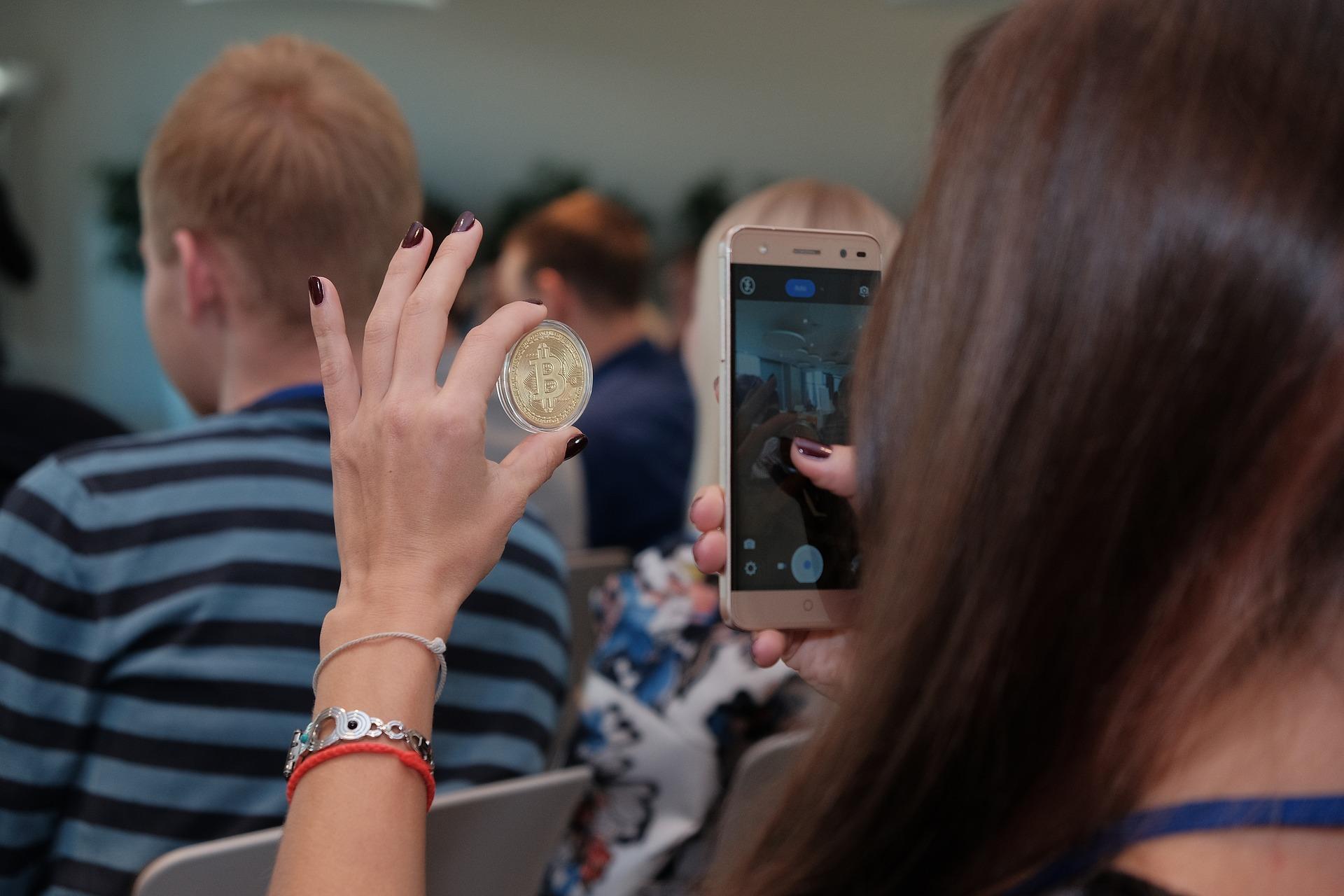 Девушка смотрит реальную золотую монету Bitcoin